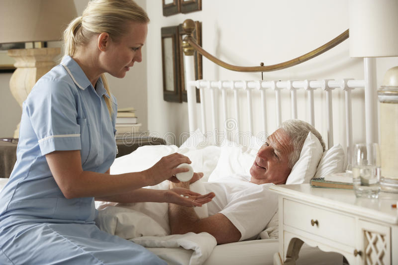 SjuksköterskaGiving Senior Male läkarbehandling i säng hemma arkivbild