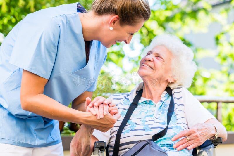 Sjuksköterskainnehavhand av den höga kvinnan i pensionhem arkivbilder