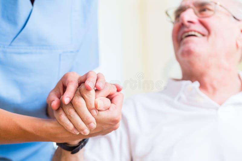 Sjuksköterskainnehavhanden av den höga mannen vilar in hemmet royaltyfria foton