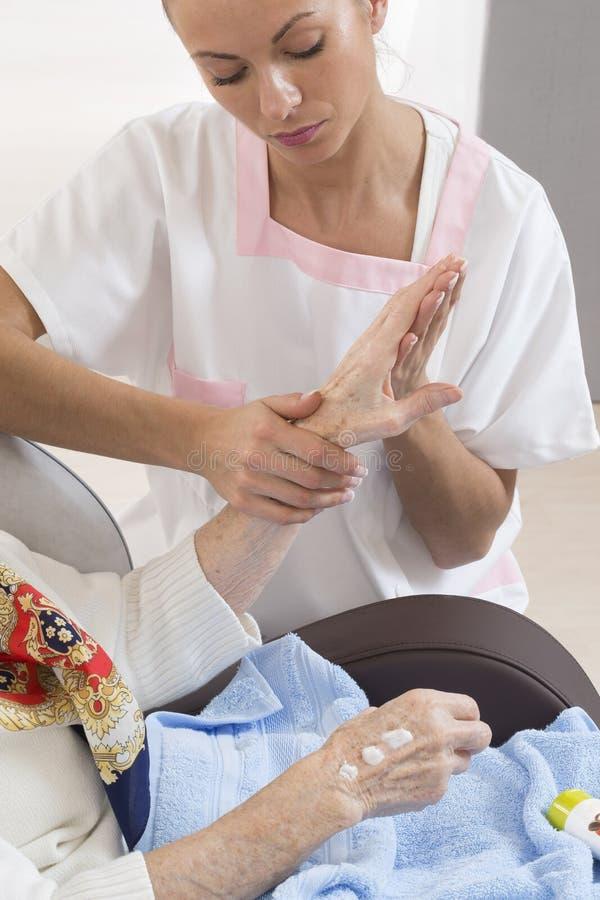 Sjuksköterskan eller anhörigvårdaren hjälper en äldre kvinna med hudomsorg royaltyfri fotografi