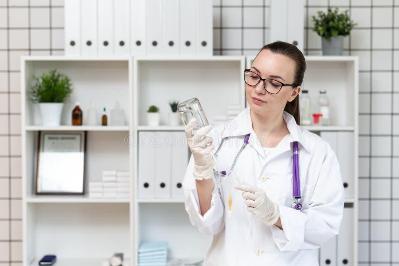 Sjuksköterskan förbereder en droppglass med en lösning av medicin arkivbild