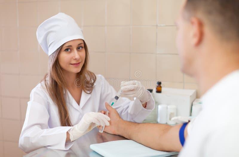 Sjuksköterskan förbereder sig att göra en intravenös injektion royaltyfri fotografi