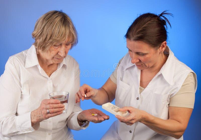 Sjuksköterskan hjälper den äldre kvinnan med att räcka ut preventivpillerar royaltyfri bild