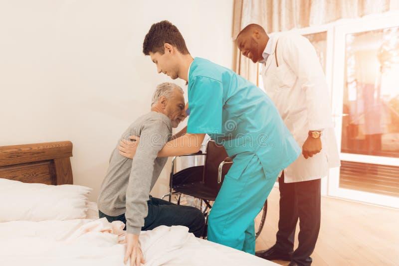 Sjuksköterskan hjälper den äldre mannen att få ut ur säng och att sitta i en rullstol arkivfoton