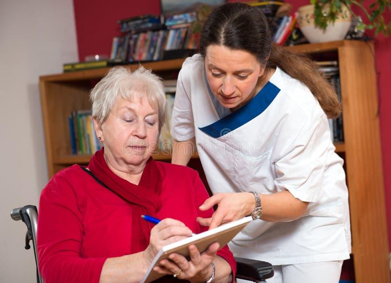 Sjuksköterskan hjälper en gammal kvinna fotografering för bildbyråer