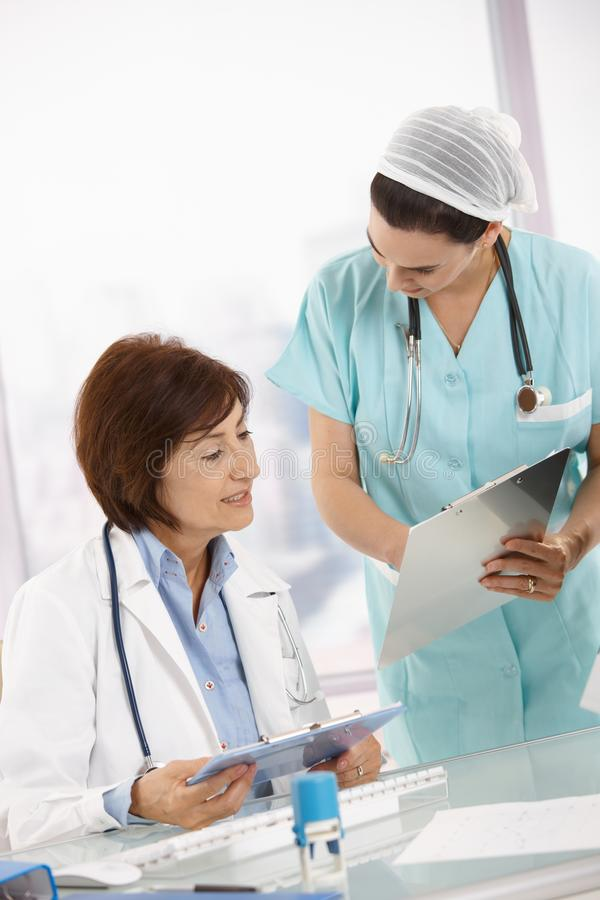 Sjuksköterskan och pensionären doctor analysering av diagnos royaltyfria foton