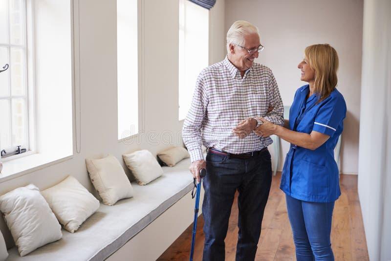 Sjuksköterskan som hjälper den höga mannen, går genom att använda en gå pinne royaltyfri foto