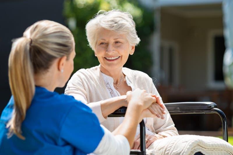 Sjuksköterskan tar omsorg av den gamla patienten arkivbilder