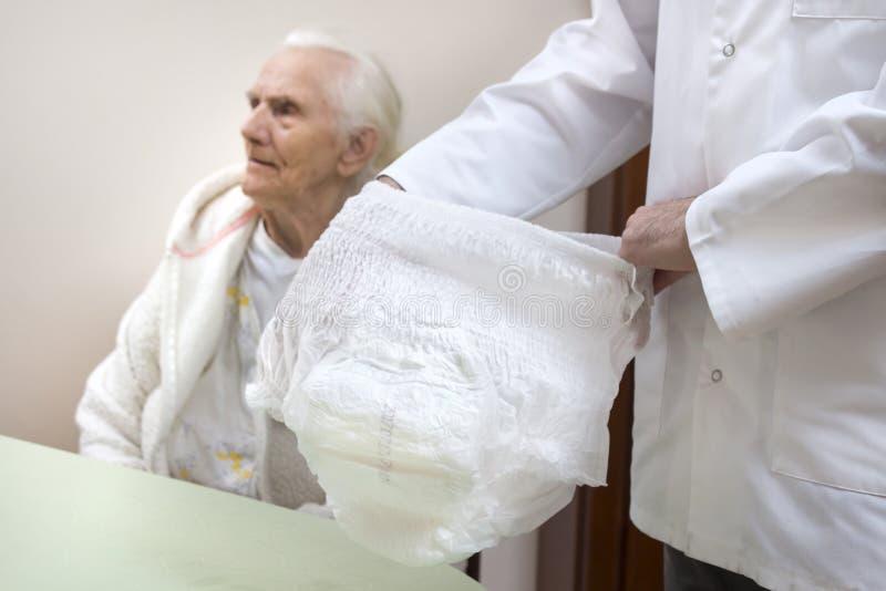 Sjuksköterskan visar blöjaflåsanden för gamla människor En gammal kvinna i en vit badrock och nattlinne sitter på en stol i bakgr arkivfoto