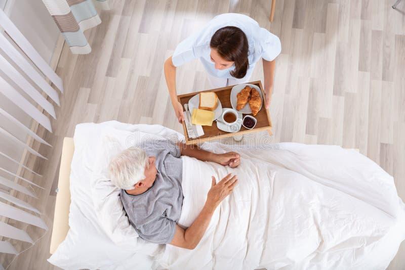 Sjuksk?terskaServing Food To h?g manlig patient i klinik arkivfoton
