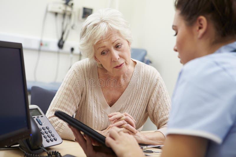 SjuksköterskaShowing Patient Test resultat på den Digital minnestavlan arkivfoton