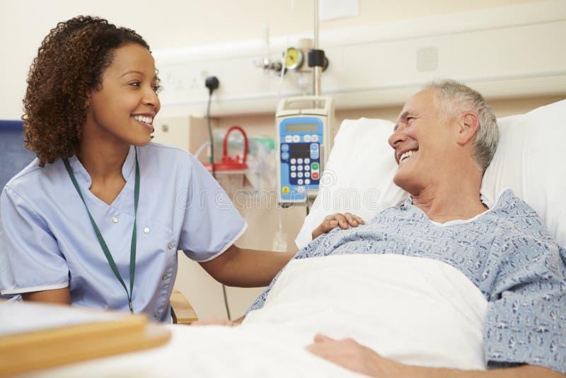SjuksköterskaSitting By Male patients säng i sjukhus arkivbilder