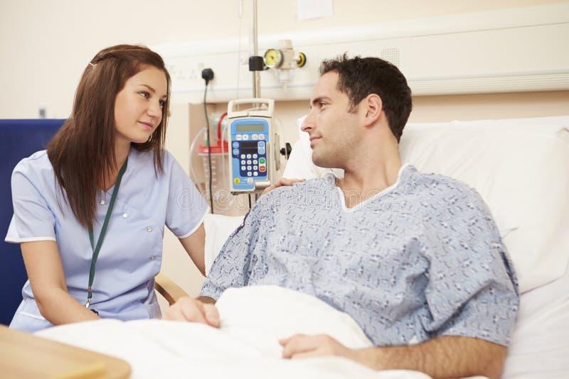 SjuksköterskaSitting By Male patients säng i sjukhus arkivbild