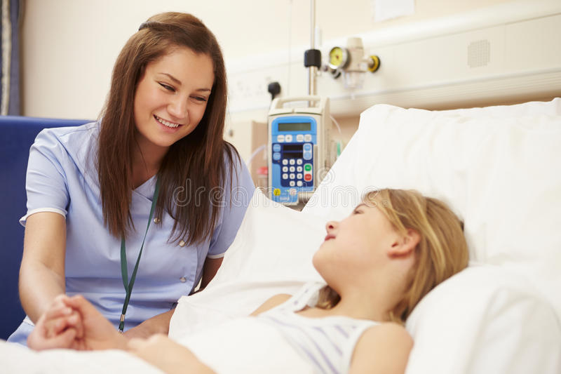 SjuksköterskaSitting By Young flickas säng i sjukhus arkivbilder