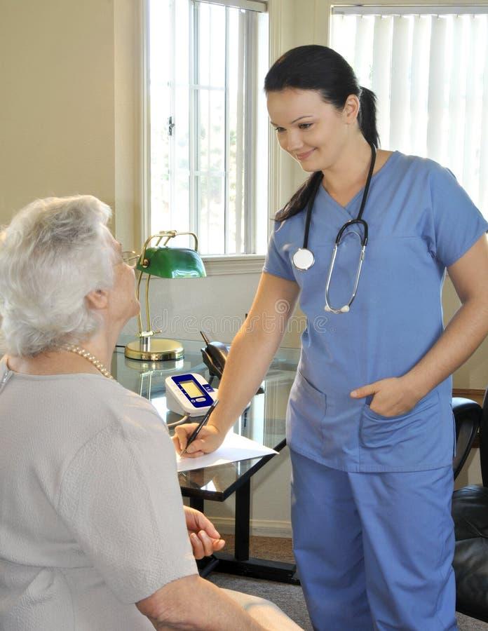 sjuksköterskatålmodigpensionär royaltyfri fotografi