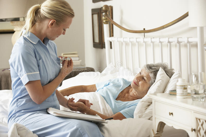 SjuksköterskaTaking Pulse Of hög tålmodig patient i säng hemma royaltyfria foton