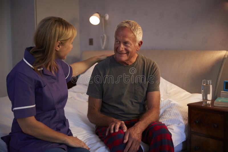 SjuksköterskaTalking With Senior man i sovrum på hem- besök arkivbilder