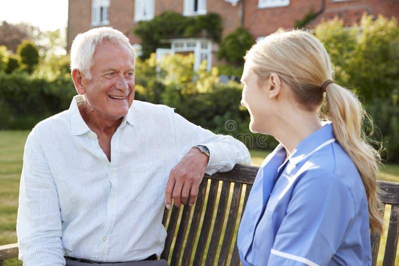 SjuksköterskaTalking To Senior man i hem för bostads- omsorg royaltyfri foto