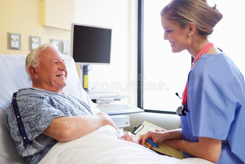 SjuksköterskaTalking To Senior manlig patient i sjukhusrum arkivfoto