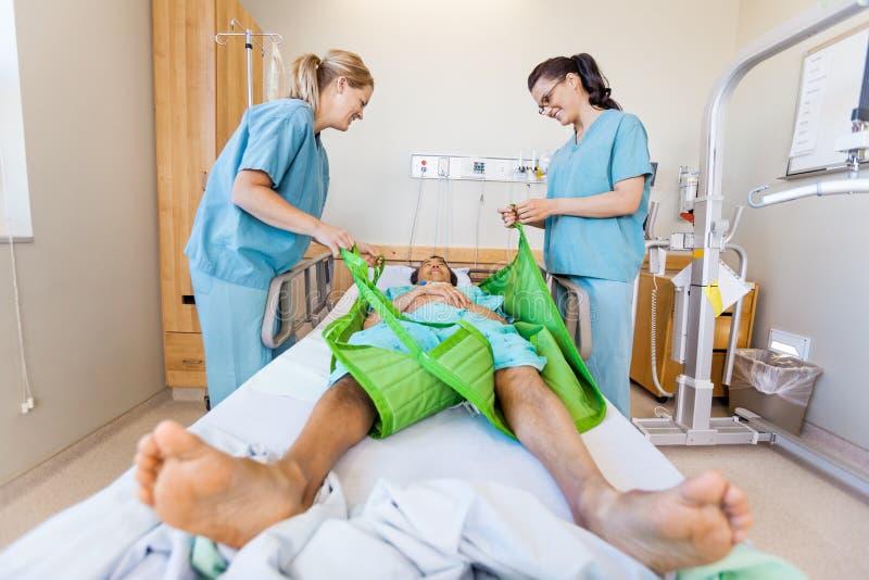 Sjuksköterskor som förbereder den manliga patienten, innan överföring royaltyfri bild