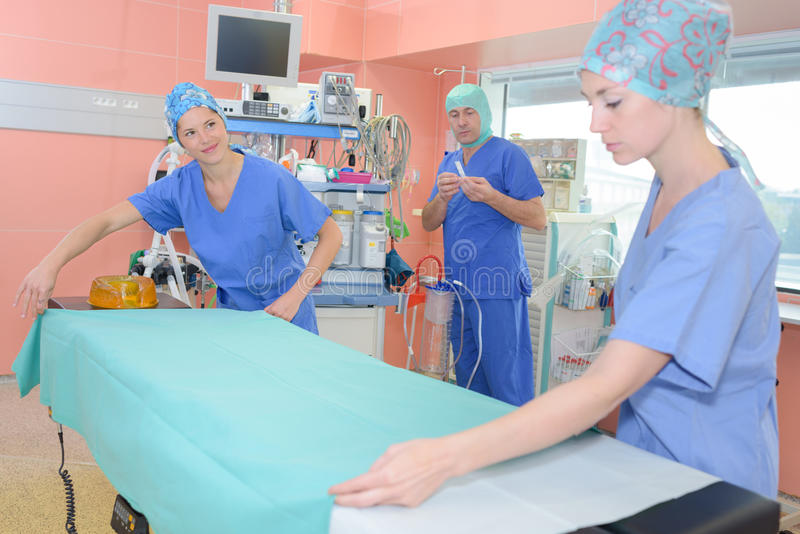 Sjuksköterskor som gör säng i sjukhus royaltyfria bilder
