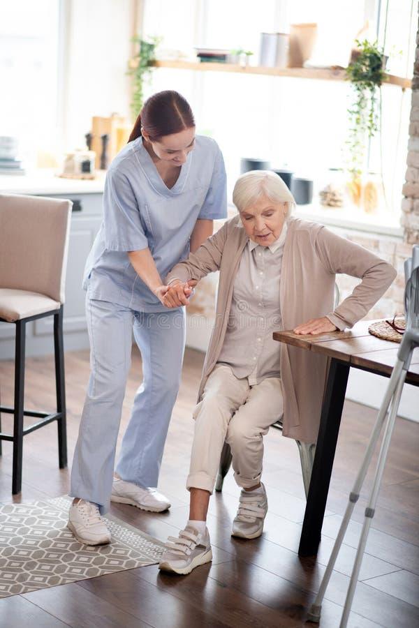 Sjuksköterskor som hjälper äldre kvinnor att vidta åtgärder efter operation royaltyfria foton