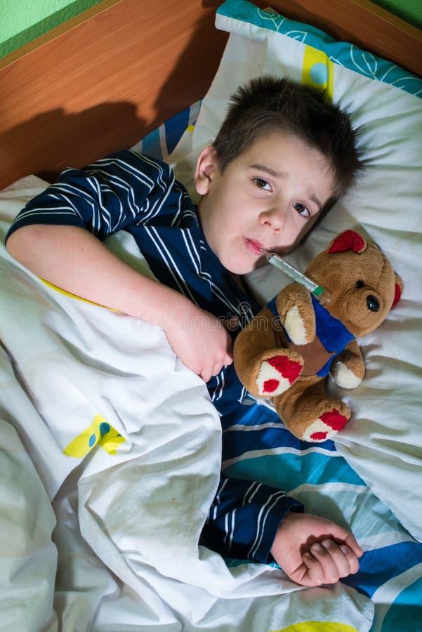 Sjukt barn i säng med nallebjörnen royaltyfria foton