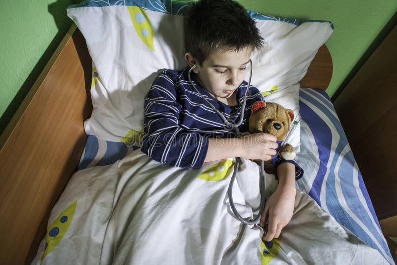 Sjukt barn i säng med nallebjörnen royaltyfria bilder