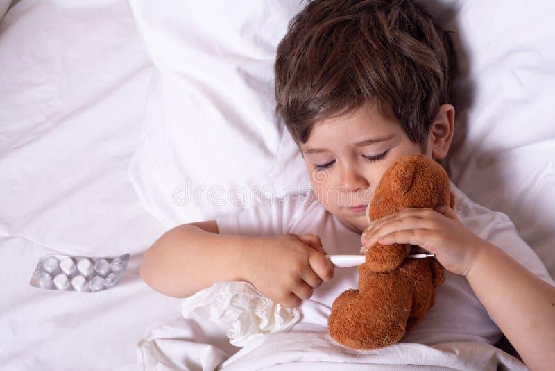 Sjukt barn med feber och sjukdom i säng som kontrollerar temperatur med termometern Ungeinfluensabehandlingar alla begreppsf?rs?k royaltyfri bild
