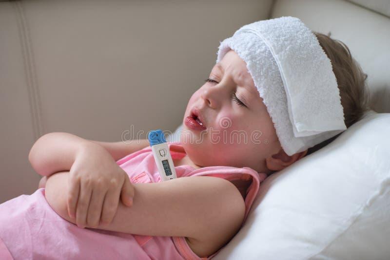 Sjukt barn med hög feber som lägger i säng arkivbilder