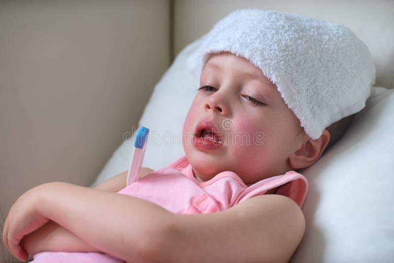 Sjukt barn med hög feber som lägger i säng arkivfoto