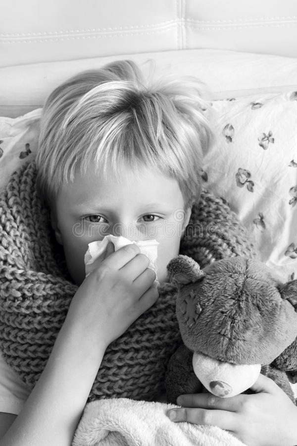 Sjukt barn med nallebjörnen fotografering för bildbyråer