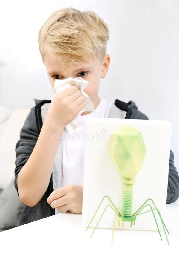 sjukt barn Pojken torkar hans näsa royaltyfria foton