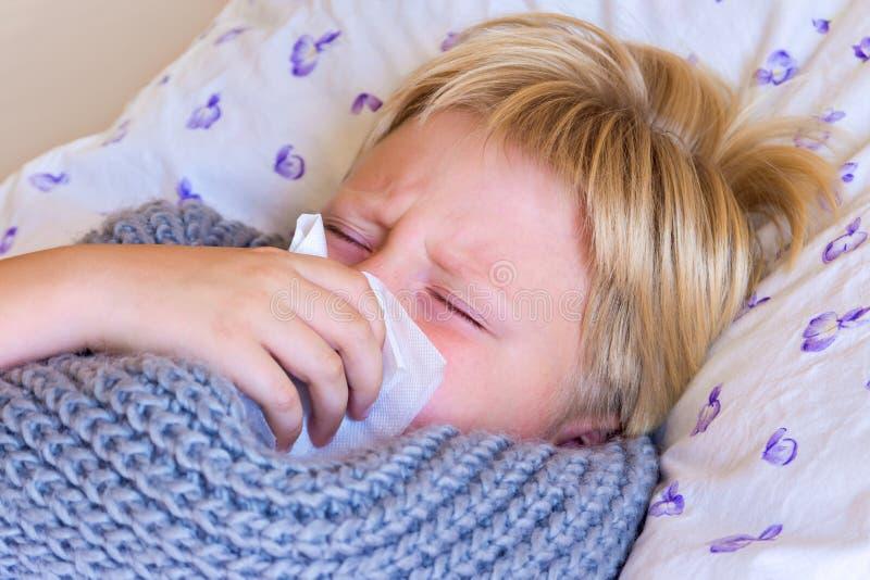 Sjukt barn som blåser näsan royaltyfri bild