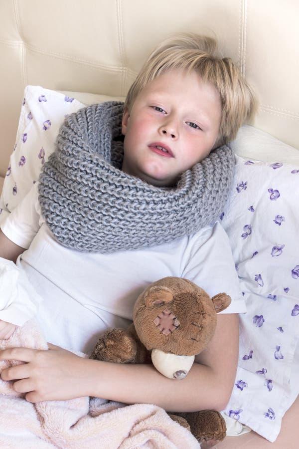 Sjukt barn som ligger i säng arkivfoto