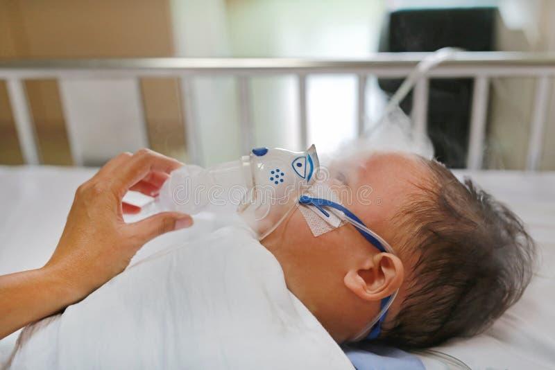 Sjukt behandla som ett barn pojken och har inandningterapi vid maskeringen av inhalatorn på tålmodig säng på sjukhuset Respirator arkivfoton