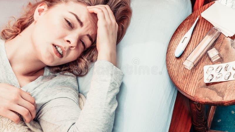 Sjukt kvinnalidande från huvudvärk smärtar arkivbild