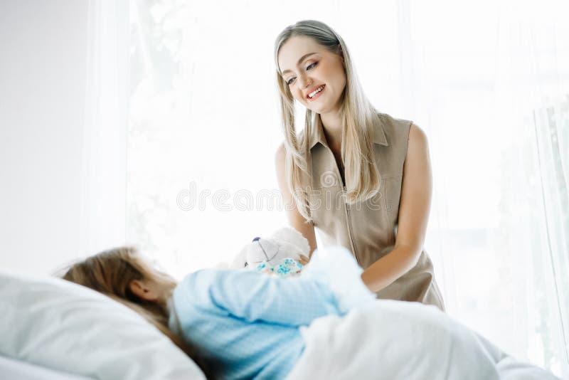 Sjukt ligga för liten flicka i säng på den geende nallebjörnen för sjukhus och moders till hennes dotter Medicinsk palliationsjuk royaltyfri foto