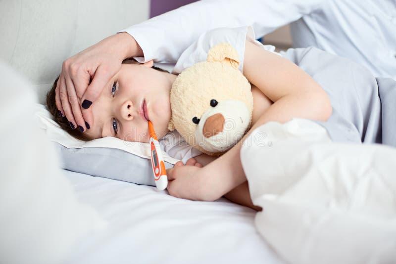 Sjukt litet barn med temperatur i säng royaltyfri bild