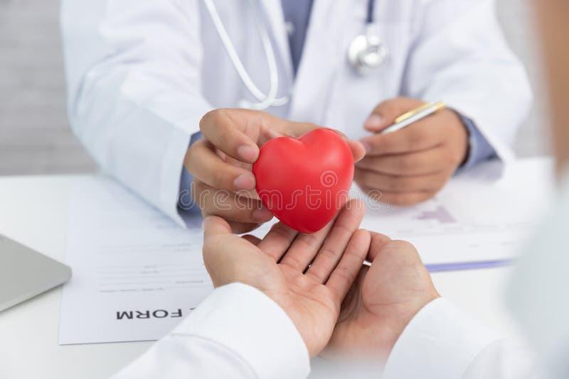 Sjukvård och medicinskt begrepp, hållande hjärtaboll för doktor och att förklara hjärtsjukdomtecken och medicinsk behandling till arkivbilder