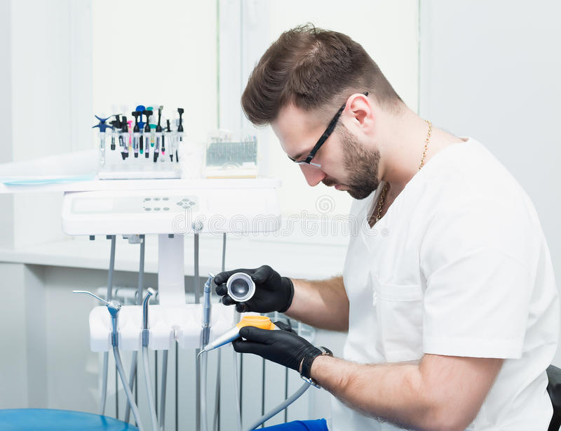 Sjukvård-, yrke-, stomatology- och medicinbegrepp - le den manliga unga tandläkaren över medicinsk kontorsbakgrund arkivbilder