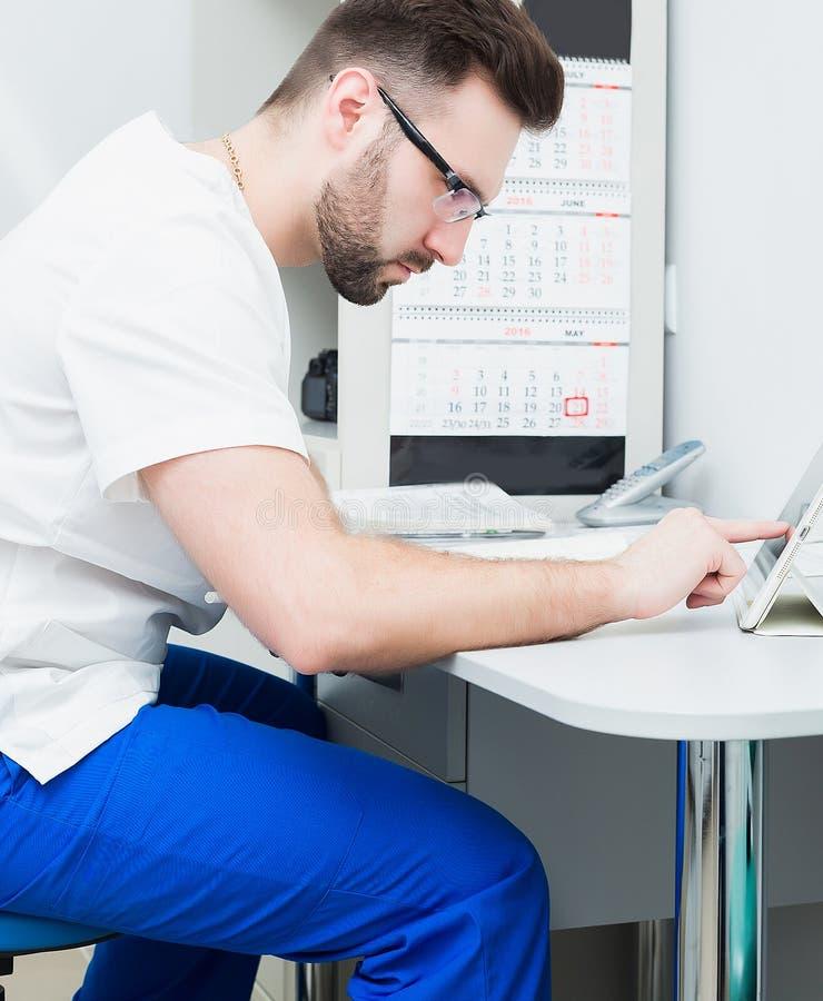Sjukvård-, yrke-, stomatology- och medicinbegrepp - le den manliga unga tandläkaren över medicinsk kontorsbakgrund arkivfoton