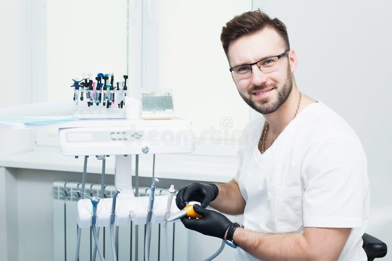 Sjukvård-, yrke-, stomatology- och medicinbegrepp - le den manliga unga tandläkaren över medicinsk kontorsbakgrund royaltyfri foto