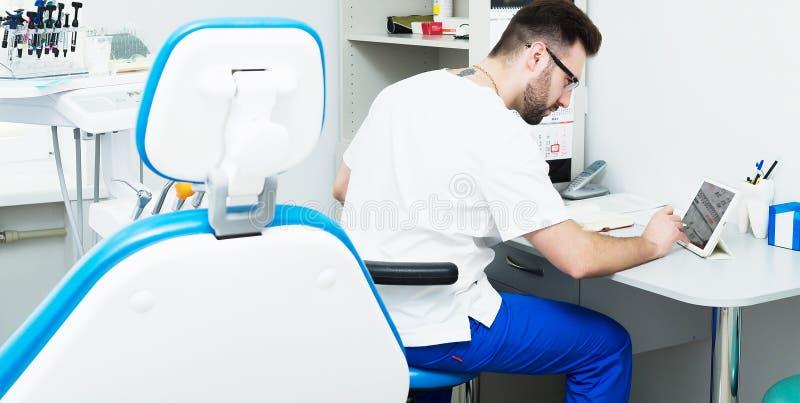 Sjukvård-, yrke-, stomatology- och medicinbegrepp - le den manliga unga tandläkaren över medicinsk kontorsbakgrund royaltyfria bilder