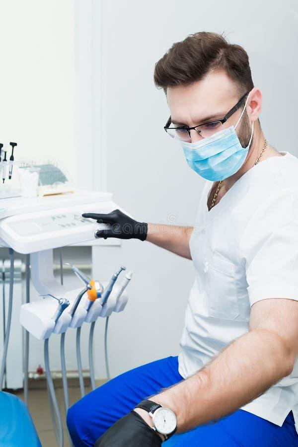Sjukvård-, yrke-, stomatology- och medicinbegrepp - le den manliga unga tandläkaren över medicinsk kontorsbakgrund royaltyfri fotografi