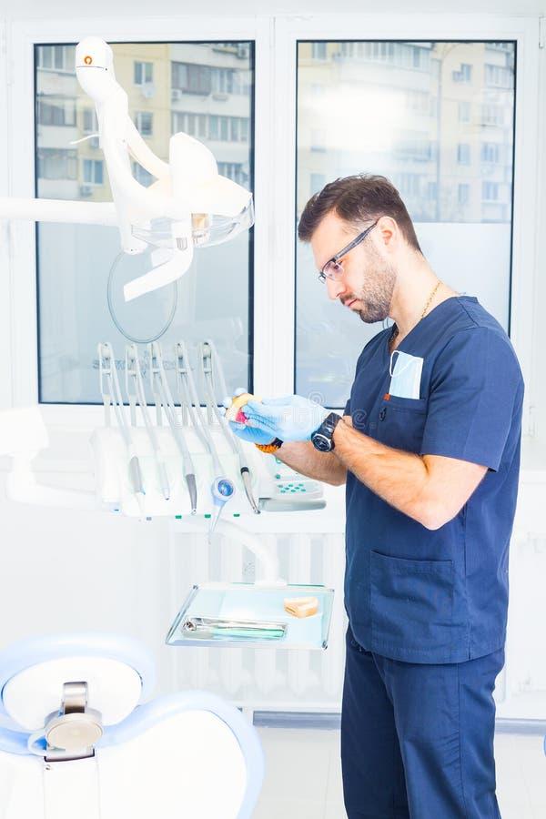 Sjukvård-, yrke-, stomatology- och medicinbegrepp - manlig tandläkare över medicinsk kontorsbakgrund royaltyfria bilder