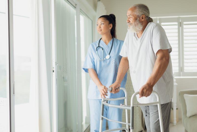 Sjukvårdarbetare med mannen som använder gå service arkivbilder