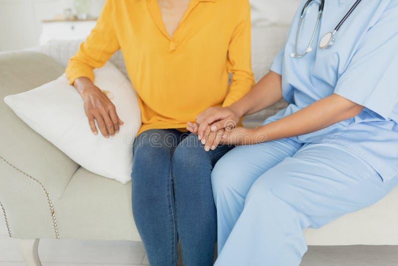 Sjukvårdarbetare och kvinna som sitter på en soffa royaltyfria bilder