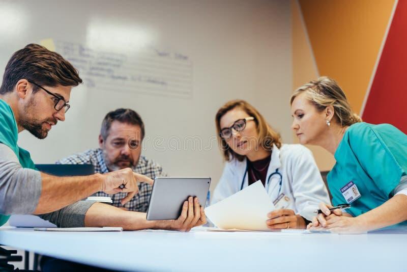 Sjukvårdarbetare som har ett möte i styrelse royaltyfria foton