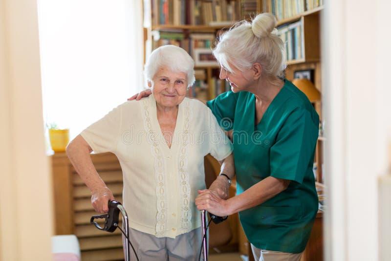 Sjukvårdassistent som hjälper den höga kvinnan med att gå ramen arkivfoto